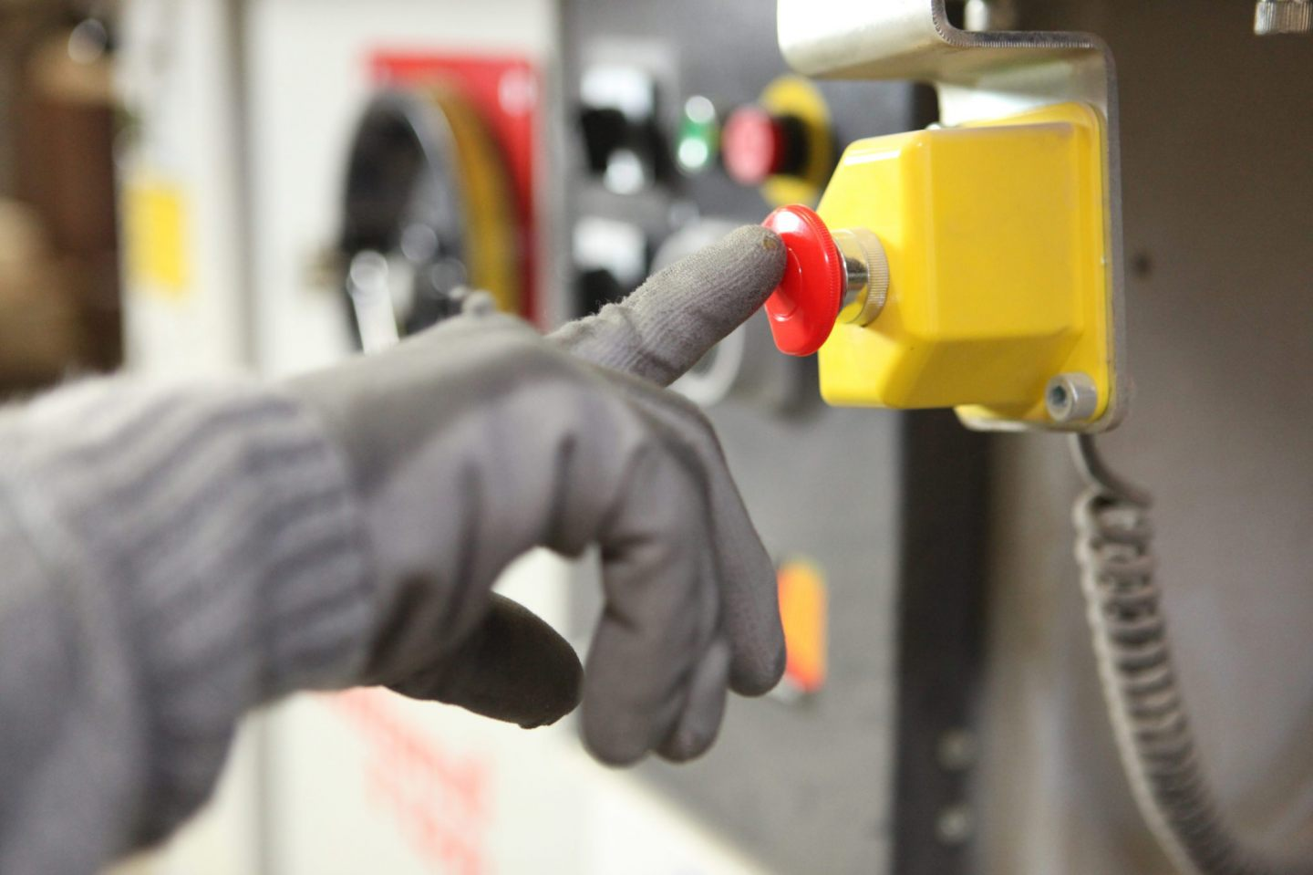 Factory worker pushing a button